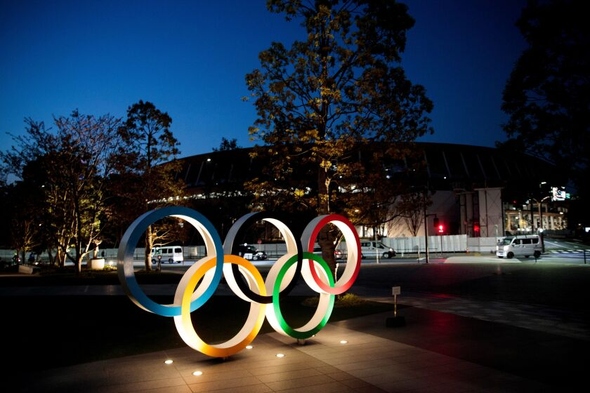 The Olympic rings are displayed outside the National Stadium in Tokyo on April 7.