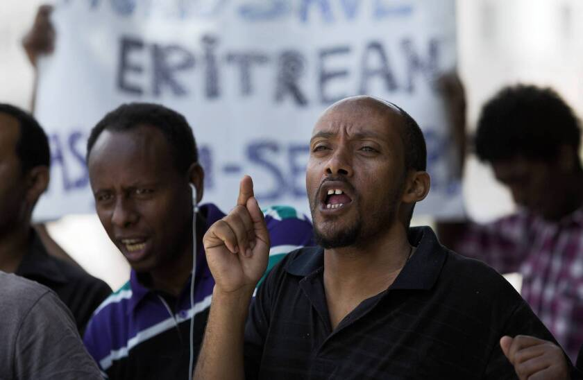 An Eritrean immigrant shouts slogans about granting refugee status to African immigrants who made their way into Israel, as a small group holds a protest outside the prime minister's office in Jerusalem last month.