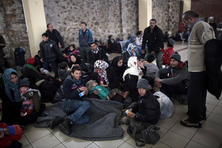 Migrant families wait in a terminal building after arriving from the Aegean Islands into the port of Piraeus, where many Afghan migrants have become stranded in Athens.