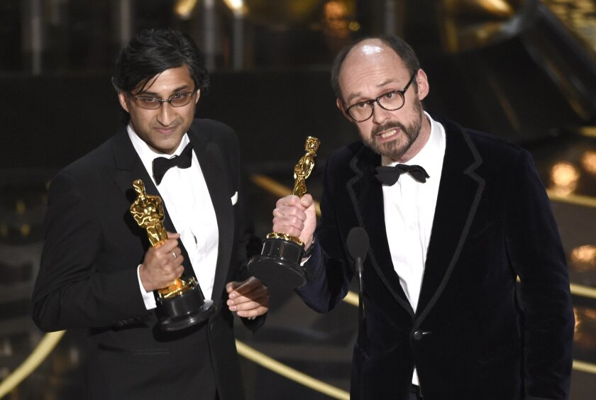 """Asif Kapadia, left, and James Gay-Rees accept the award for best documentary feature for """"Amy"""" at the Oscars on Sunday, Feb. 28, 2016, at the Dolby Theatre in Los Angeles. (Photo by Chris Pizzello/Invision/AP)"""