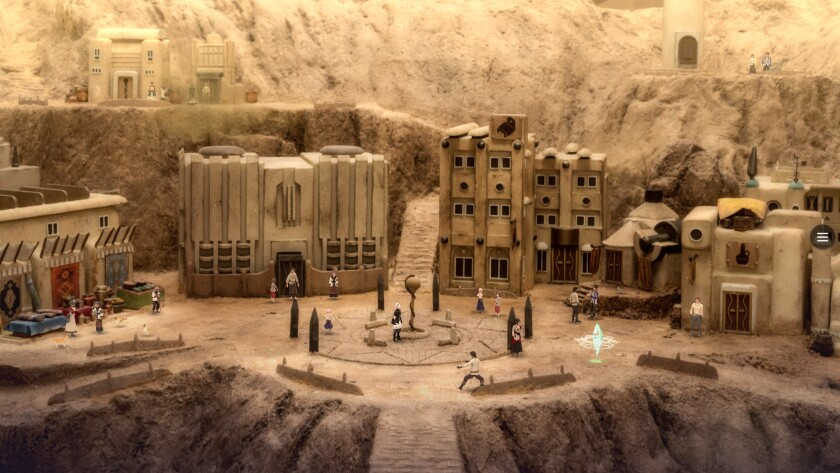 A diorama with miniature buildings and figures in a desert-type setting.