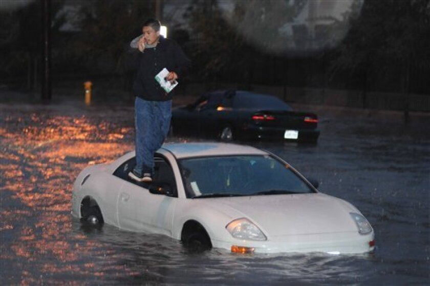 Victor Lopez of Ontario, Calif., calls for help from the top of his car early Monday, Dec. 15, 2008, after his car stalled while trying to cross a flooded intersection in Ontario, Calif. A powerful storm in California snarled roads, caused two traffic fatalities, collapsed the roof of an occupational school and forced hundreds of people to flee their homes in a suburb devastated by wildfire just last month. (AP Photo/Walter Weiss)