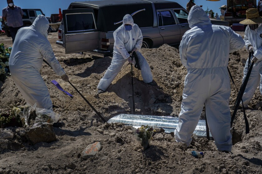Workers in protective suits lower a coffin containing the remains of woman, who died of COVID-19, at a cemetery in Tijuana.