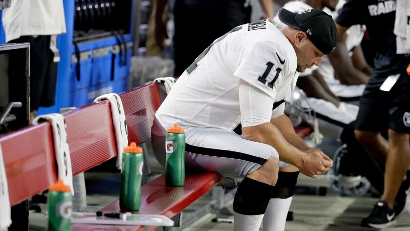 Oakland Raiders kicker Sebastian Janikowski sits on the bench after missing a field-goal attempt aga