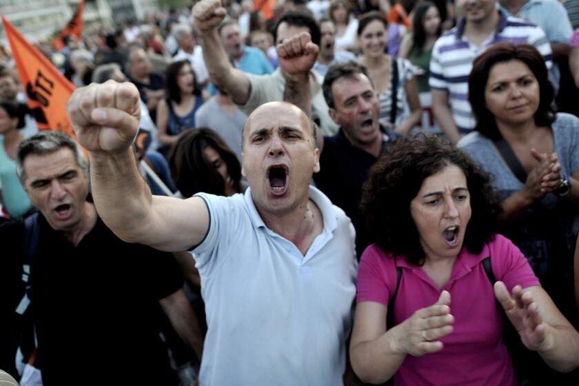 Municipal employees shout slogans against the Greek government in front of Parliament in Athens as lawmakers prepared to vote late Wednesday on a controversial new austerity package involving a huge shake-up of the civil service, with thousands of jobs on the line.