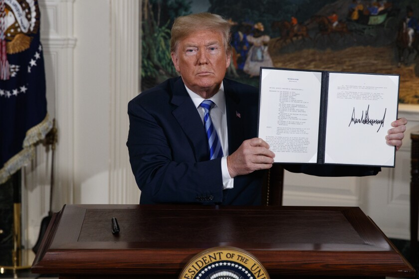 FILE - In this May 8, 2018 file photo, President Donald Trump shows a signed Presidential Memorandum after delivering a statement on the Iran nuclear deal from the Diplomatic Reception Room of the White House. The decision Tuesday, Jan 14, 2020, by European nations to trigger a dispute resolution mechanism in the Iran nuclear deal marks the latest step in the unraveling of the accord, which began when President Donald Trump walked away from the agreement and began restoring sanctions on Iran. (AP Photo/Evan Vucci, File)