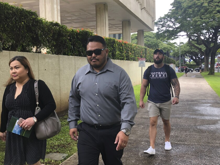 Former Honolulu police officer Reginald Ramones, center, walks down a street in Honolulu on Wednesday, Sept. 25, 2019. Ramones has pleaded guilty to failing to report that another police officer forced a homeless man to lick a public urinal. (AP Photo/Jennifer Sinco Kelleher)