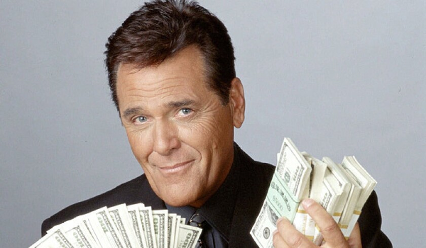 Chuck Woolery poses with his hands full of money.
