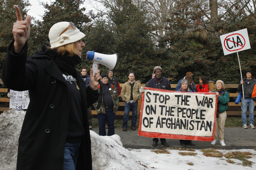 Cindy Sheehan points down the road toward former Vice President Dick Cheney's house during an antiwar protest in 2010.