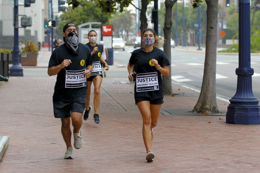 """Runners make their way down Broadway on Saturday during a 5k run to show """"Unity for Breonna Taylor."""""""