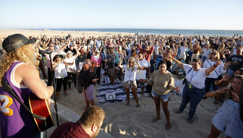 Hundreds gathered for the Saturate OC worship event held north of the pier in Huntington Beach, on Friday, July 10.