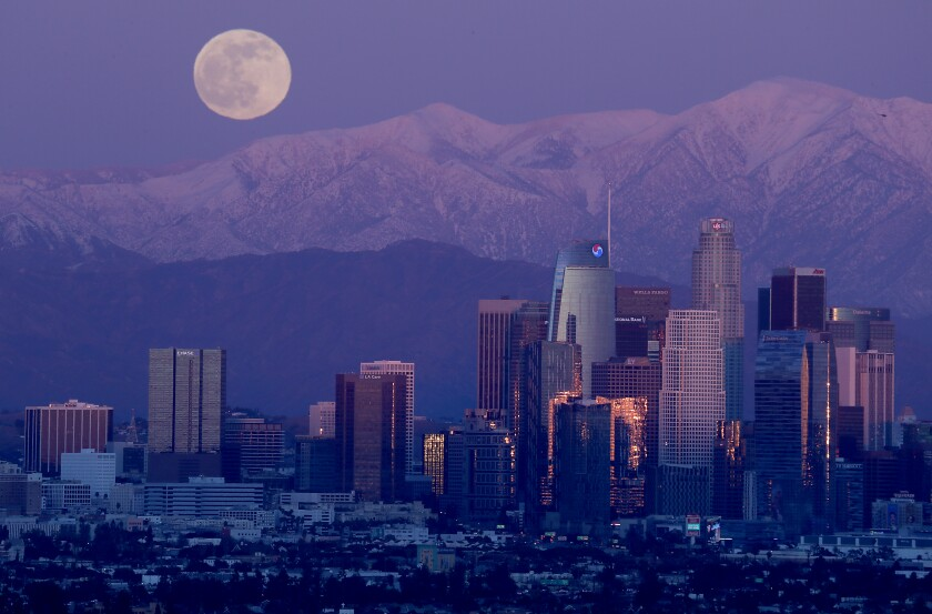 A full moon rises over the snow-capped San Gabriel Mountains and the skyline of downtown Los Angeles
