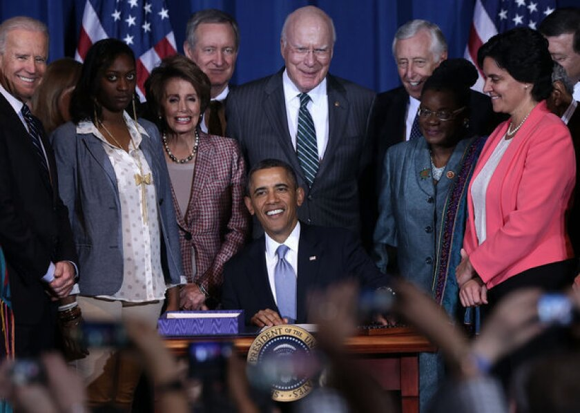 President Obama signs the Violence Against Women Act into law at the Department of the Interior in Washington.