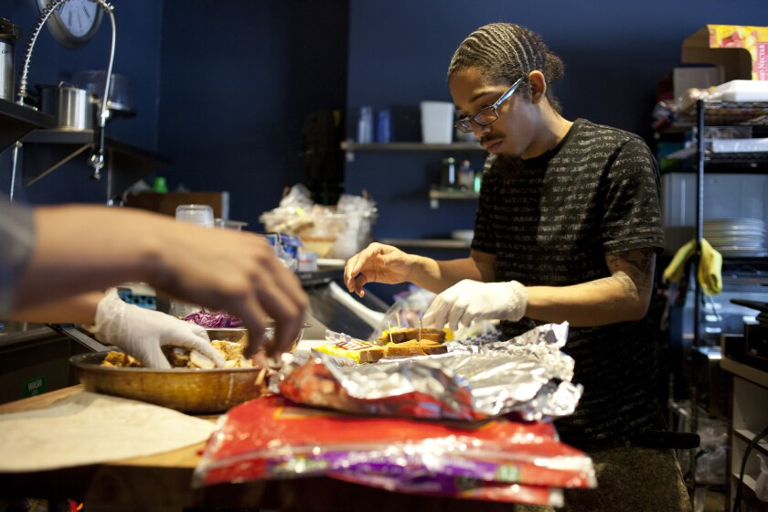 Employee Keenan Leal, 23, prepares food at the Manifesto Cafe in Los Angeles on April 9.