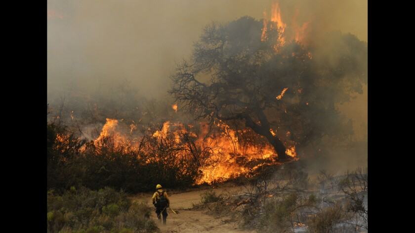 A Santa Barbara County firefighter heads toward the wildfire near Lompoc.