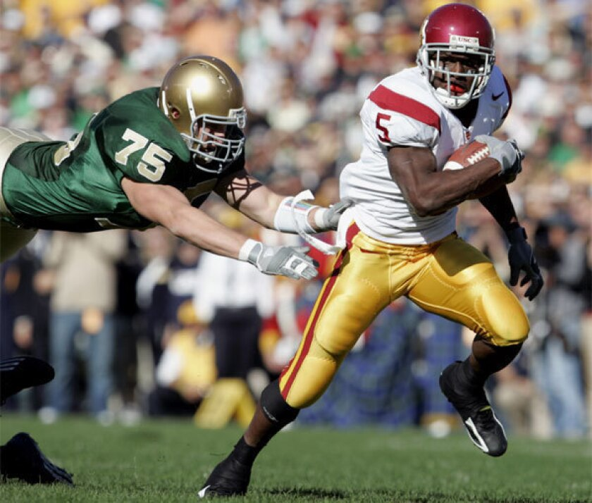 USC running back Reggie Bush jumps away from Notre Dame's Chris Frome while making his way to the end zone in 2005 at College Stadium in South Bend, Ind.