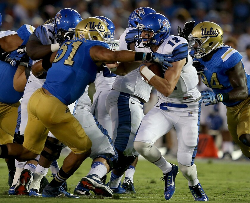 UCLA linebacker Aaron Wallace pressures Memphis quarterback Paxton Lynch in the first quarter.