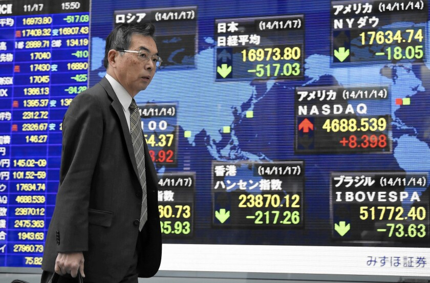 A man walks past a stock market indicator board Monday in Tokyo. Japan's benchmark Nikkei 225 stock market index slumped nearly 3%, but other global markets shrugged off the news.