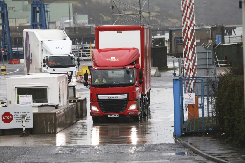 Vehicles leave the port of Larne, Northern Ireland, Tuesday, Feb. 2, 2021. Authorities in Northern Ireland have suspended post-Brexit border checks on animal products and withdrawn workers after threats against border staff.(AP Photo/Peter Morrison)