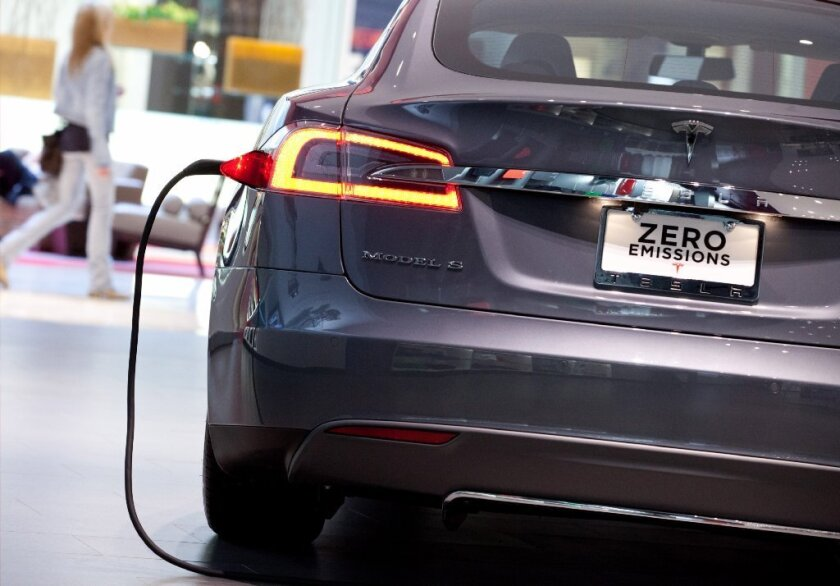 A Tesla Motors Inc. Model S connected to a charger sits on display at the company's store at the Short Hills Mall in Short Hills, N.J.