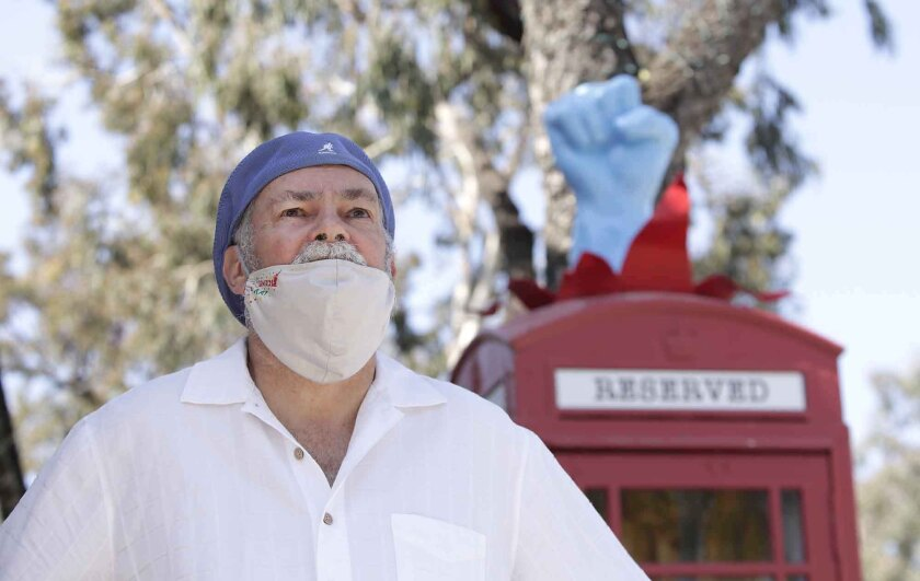 """Laguna Beach artist Robert Holton stands next to his """"Superhero Changing Station"""" on Forest Avenue, where it has been altered to thank first responders, medical staff and all essential workers during the coronavirus pandemic."""