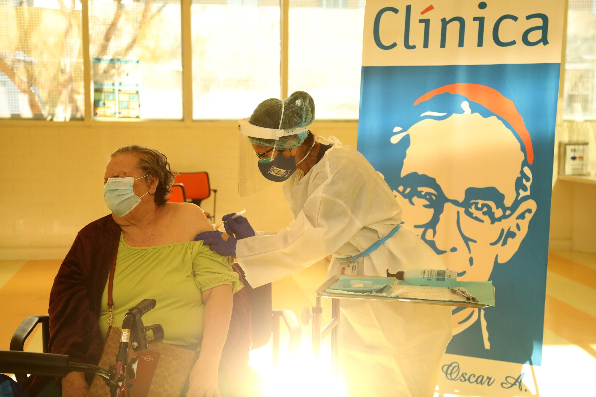 Ana Canales, 78, receives the Moderna COVID-19 vaccine from medical assistant Licelda Perez at Clínica Romero.