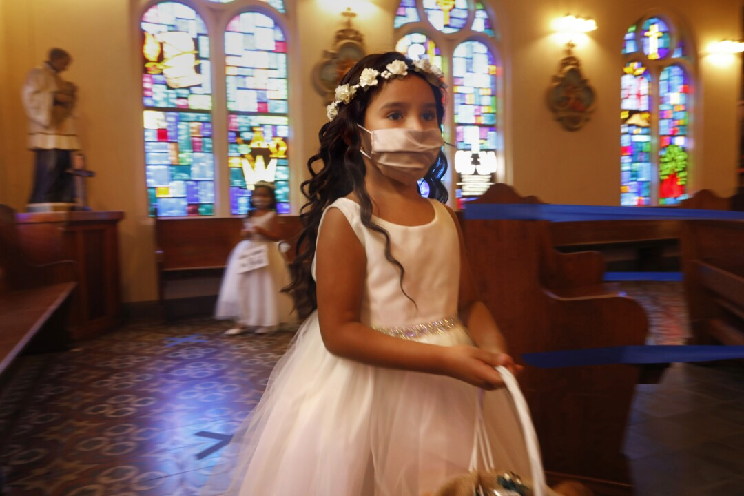 Flower girl Drea Cedillo, 5, wears a mask during a family wedding Saturday in Mission, Texas.
