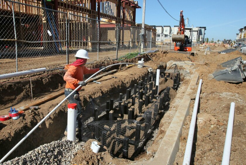 Worker Jose Vasquez installs pipe in the new Silva Cell storm water management system along Armorlite Drive on Tuesday. Construction to overhaul Armorlite between Bingham Drive and Las Posas Road might be complete by late summer. The final work will include bike lanes and wide sidewalks.