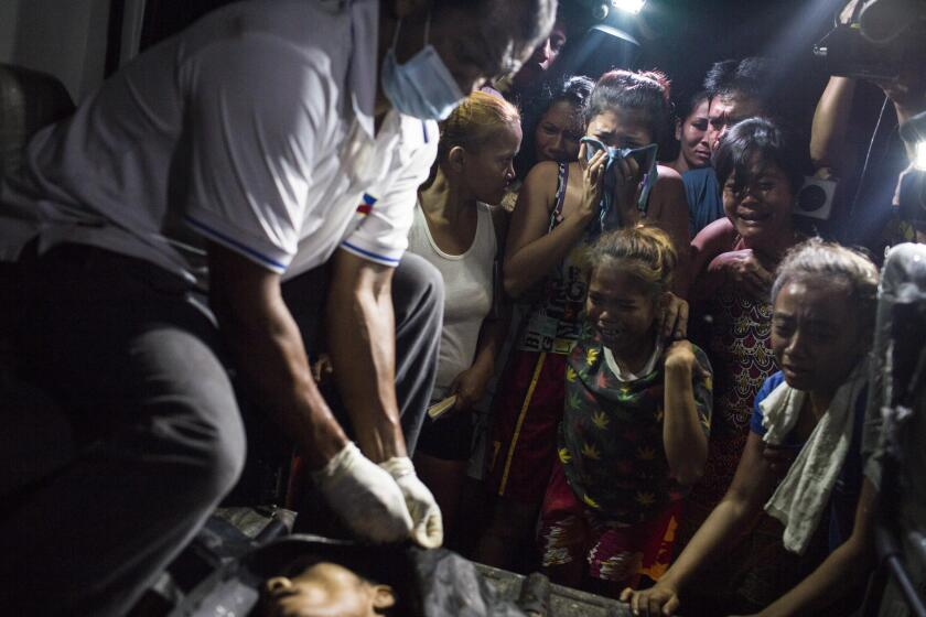 Relatives gather to mourn a slain man