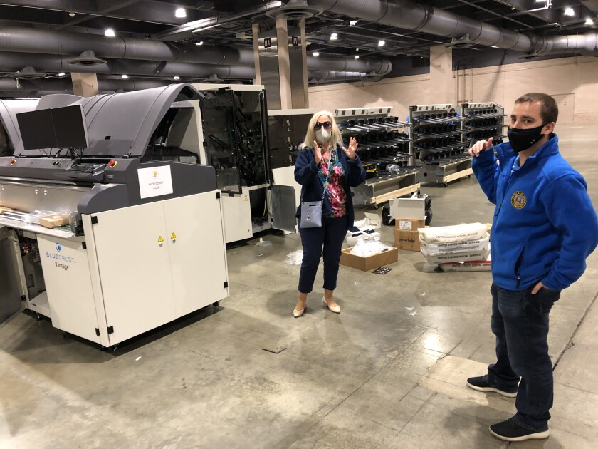 Lisa Deeley and Nick Custodio of Philadelphia's election commission next to the city's ballot-counting machinery.
