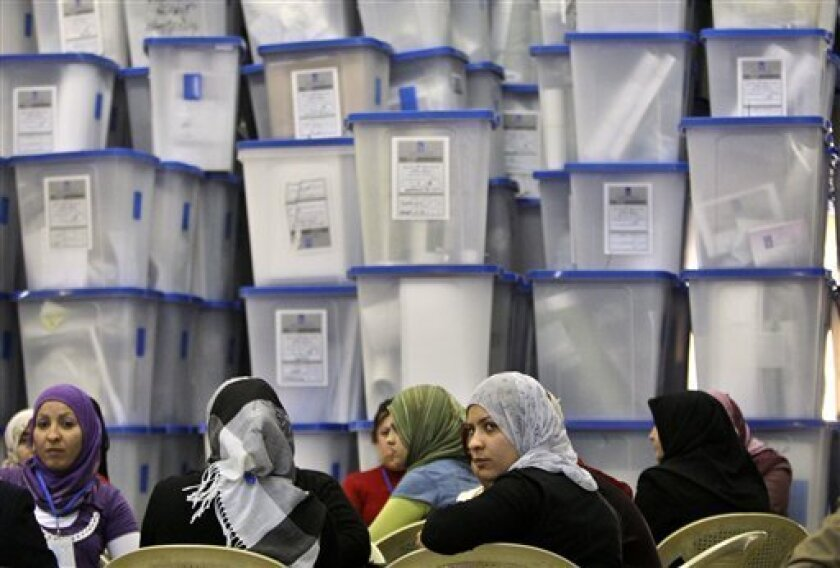 Electoral workers sit in front of piles of ballot boxes at a counting center in Baghdad, Iraq, Monday, March 8, 2010. The conclusion of Sunday's vote does not spell an immediate end to Iraq's political uncertainty, as it could be days until results come in and with the fractured nature of Iraqi politics, months to form a government. (AP Photo/Karim Kadim)