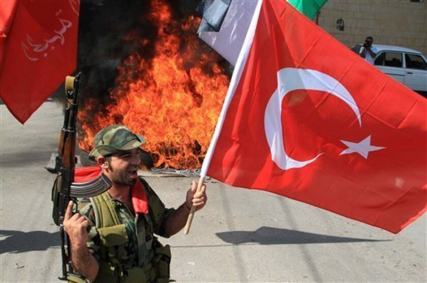 A Palestinian militant from the Democratic Front for the Liberation of Palestine, waves a Turkish flag in front of burning tires at the entrance of the Palestinian refugee camp of Ein el-Hilweh, near the southern port city of Sidon, Lebanon, Tuesday, June 1, 2010, during a protest against Israel's