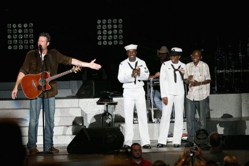 Country singer Blake Shelton (left) and JCPenney honored a military USO family, Roland Kiendrebeogo, his wife Marie Esther Kiendrebeogo, and their son Oswald Kiendrebeogo, 14, during Shelton's concert at the Sleep Train Amphitheatre on Sept. 6, 2014. (Photo by Robert Benson/Getty Images for JCPenne