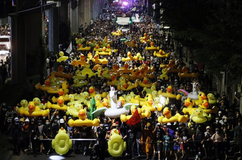 Protesters carry inflatable yellow ducks, which have become good-humored symbols of resistance during anti-government rallies, while marching towards the base of the 11th Infantry Regiment,a palace security unit under direct command of the Thai king, Sunday,Nov. 29, 2020 in Bangkok, Thailand. Pro-democracy demonstrators are continuing their protests calling for the government to step down and reforms to the constitution and the monarchy, despite legal charges being filed against them and the possibility of violence from their opponents or a military crackdown. (AP Photo/Sakchai Lalit)