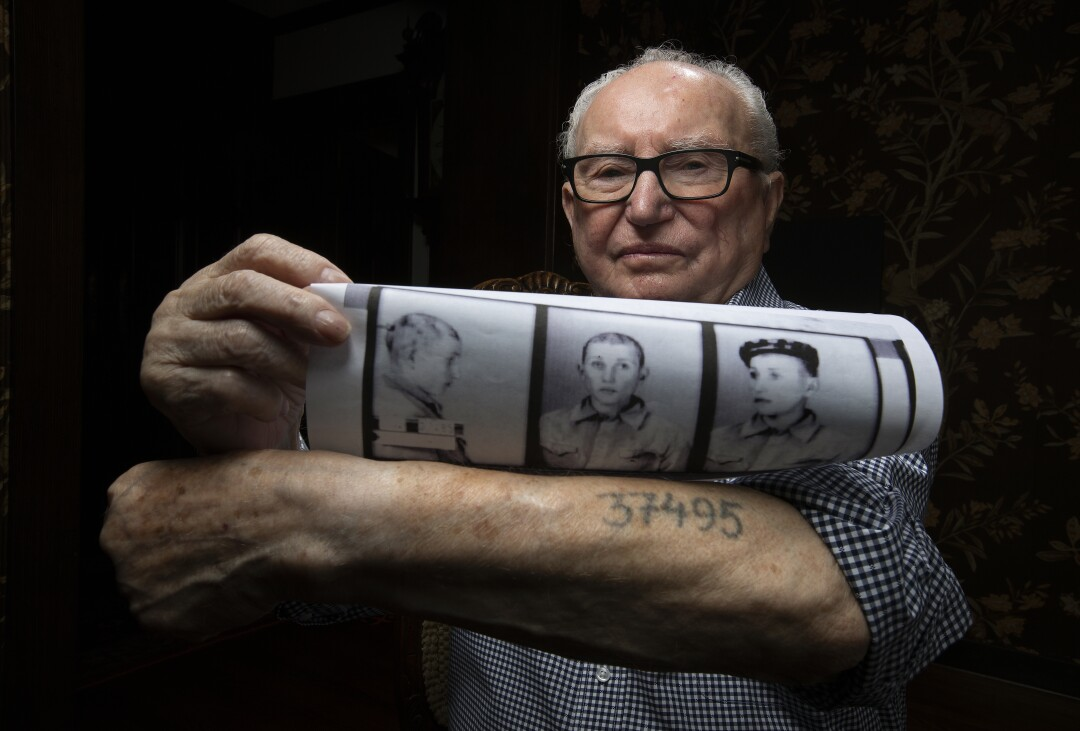 Ralph Hakman shows prisoner photos of himself from 1942, along with his prisoner number that was tattooed on his left arm.