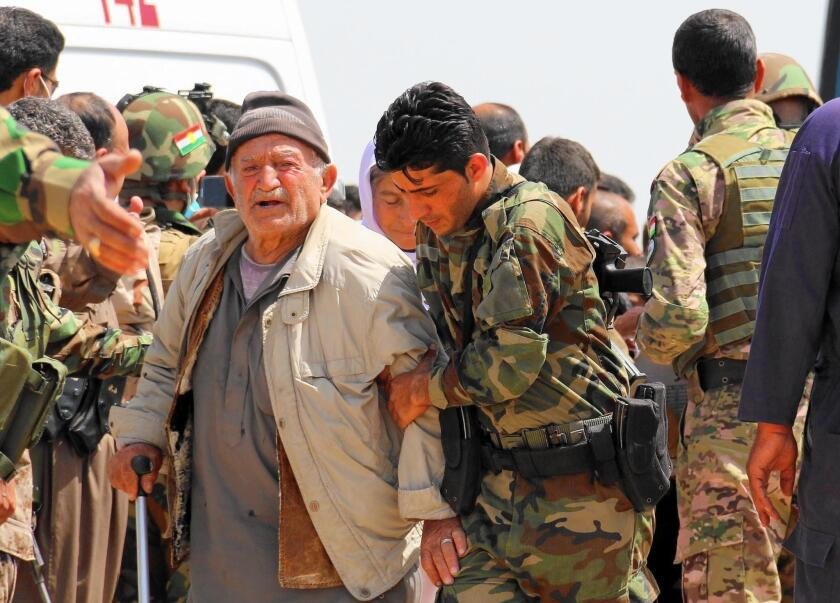 Kurdish peshmerga forces help people from Iraq's Yazidi minority in the village of Humeira, southwest of Kirkuk, on April 8, 2015 after they were released by Islamic State.