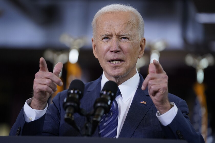President Biden pointing his fingers as he speaks into two microphones.