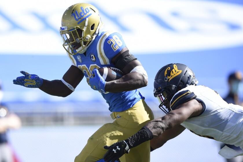 UCLA running back Brittain Brown gets past California safety Elijah Hicks on a 31-yard touchdown Nov. 15, 2020.