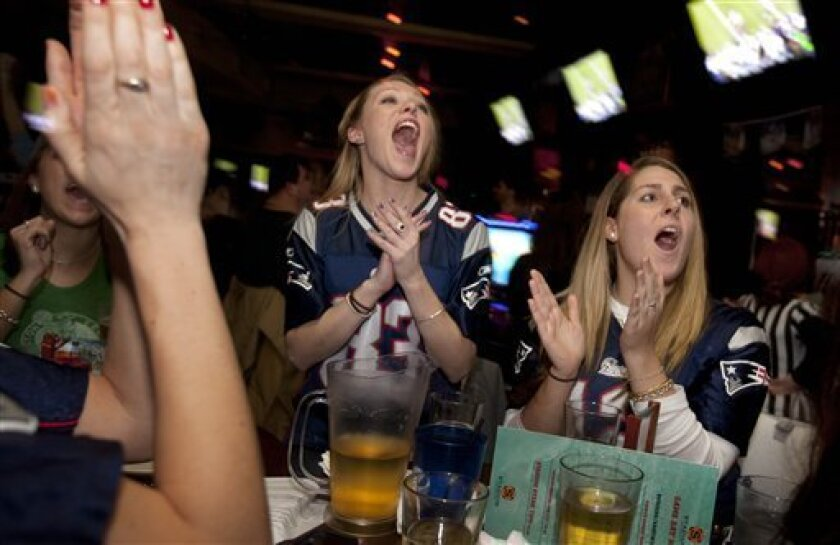Kerry Harrington, center, and Sara Laporte, right, both of Boston, react while watching, at a bar in Boston, the broadcast of the NFL football Super Bowl between the New York Giants and the New England Patriots, Sunday, Feb. 5, 2012. (AP Photo/Michael Dwyer)