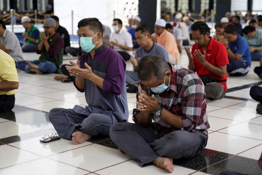 Malaysian Muslims prays during Friday prayers which was held with shorter sermons to prevent the spread of new coronavirus at the National Mosque in Kuala Lumpur, Malaysia, Friday, March 13, 2020. For most people, the new coronavirus causes only mild or moderate symptoms. For some it can cause more severe illness. (AP Photo/Vincent Thian)