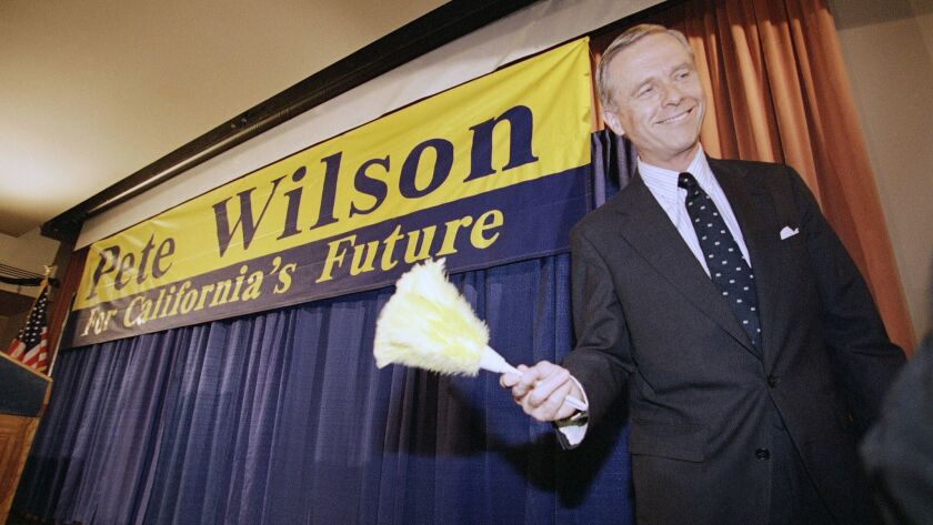 California Gov. Pete Wilson smiles after being handed a feathered duster following a news conference