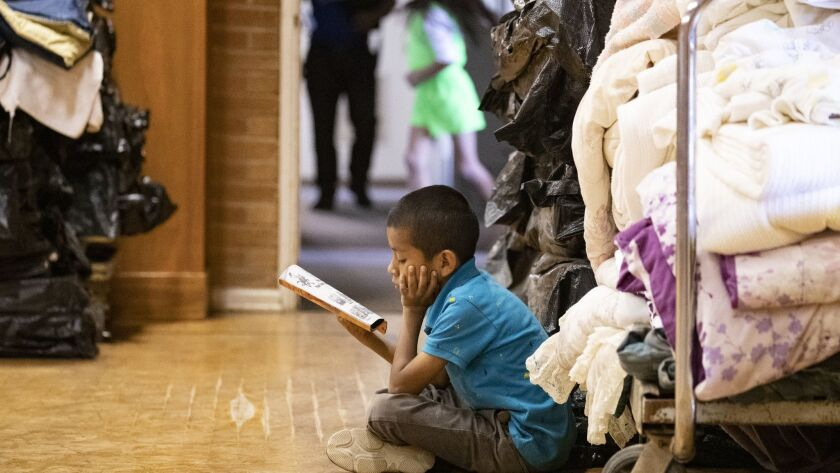Danny Ventura, 7, from Guatemala, reads a book while staying at Blythe Central Seventh-Day Adventist Church.