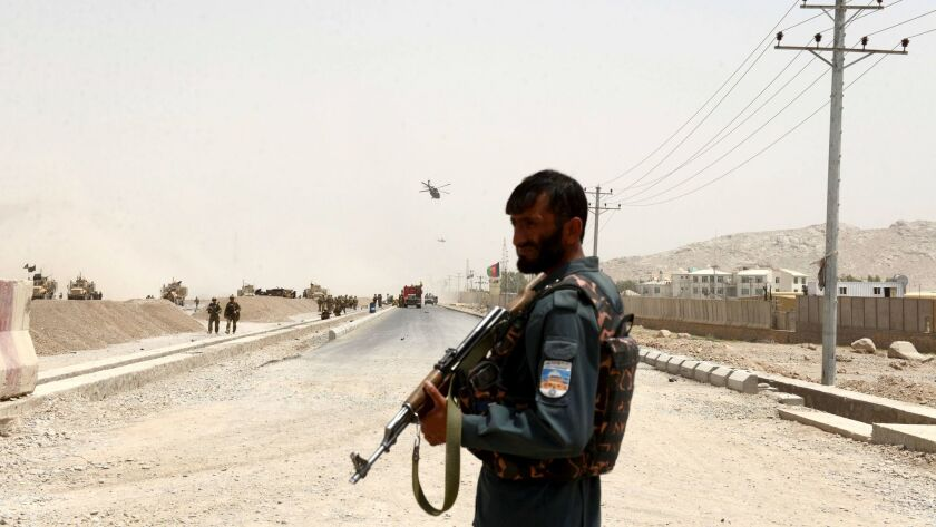 FILE - In this Wednesday, Aug. 2, 2017 file photo, An Afghan policeman stands guard near to the site