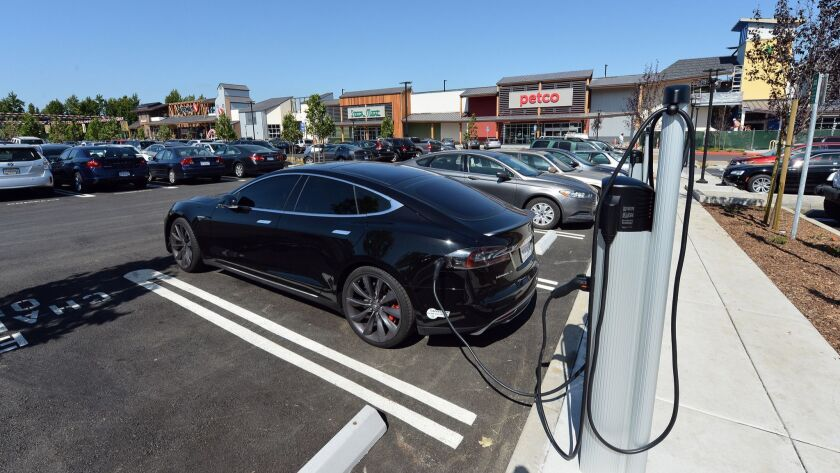 A Tesla charges at one of the electric-vehicle charging stations in the Orchards shopping center in Walnut Creek, Calif.