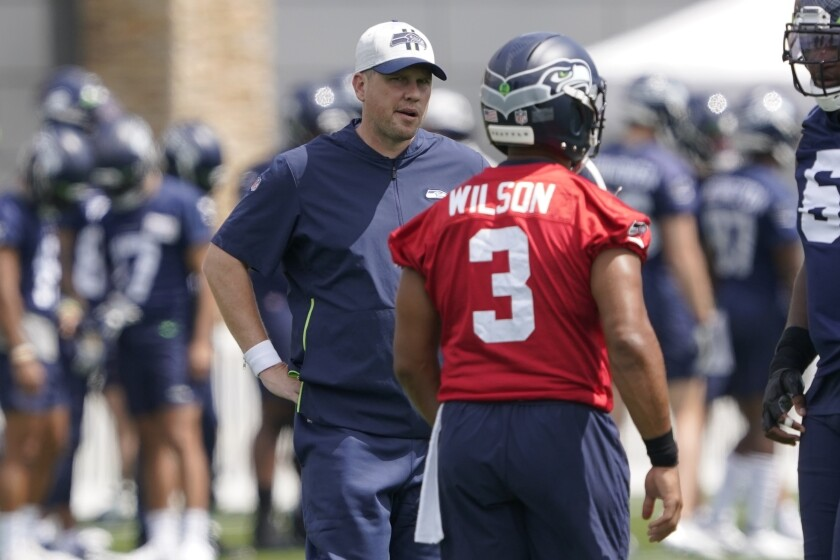 FILE - In this July 28, 2021, file photo, Seattle Seahawks offensive coordinator Shane Waldron, left, talks with quarterback Russell Wilson during NFL football practice in Renton, Wash. When the Seahawks brought Shane Waldron on board as offensive coordinator this offseason, they were hoping to pull some of what worked so well for the division rival Los Angeles Rams and implement it into a system run by Russell Wilson. The test of how well that's worked for Seattle comes on Thursday, Oct. 6, facing the Rams.(AP Photo/Ted S. Warren, File)