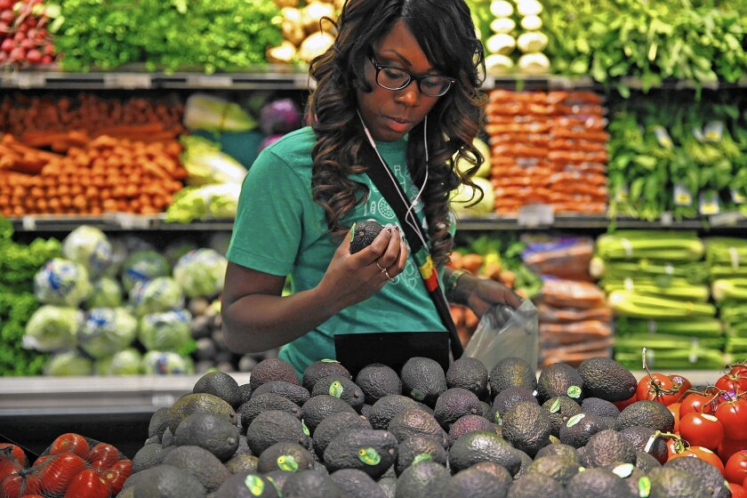 Instacart shopper Kara Pete looks over avocados at a Whole Foods Market in Sherman Oaks in September. Is it ethical to pay others to face coronavirus risks we'd rather avoid?