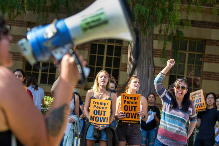 """Francisca Vergara, right, yells anti-Trump slogans with protesters during a demonstration outside UCLA's Moore Hall where Donald Trump Jr. was expected to speak while on tour for his new book """"Triggered,"""" in Los Angeles, Sunday, Nov. 10, 2019. (Brian van der Brug/Los Angeles Times via AP)"""