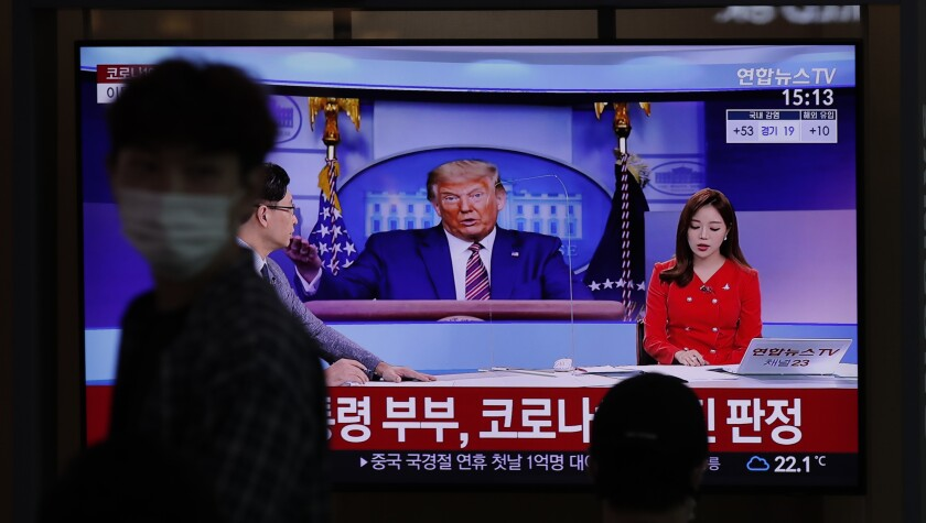 A commuter at the Seoul Railway Station walks past a TV screen featuring coverage of President Trump.