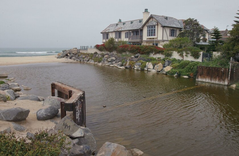 A house on the south end of the beachfront St. Malo development in Oceanside stands next the west end of the Buena Vista Lagoon. The structure under the water is the lagoon's weir.