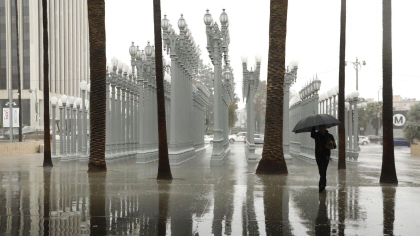 """A lone pedestrian walks in the rain toward the """"Urban Light"""" sculpture outside the Los Angeles County Museum of Art on Thursday."""